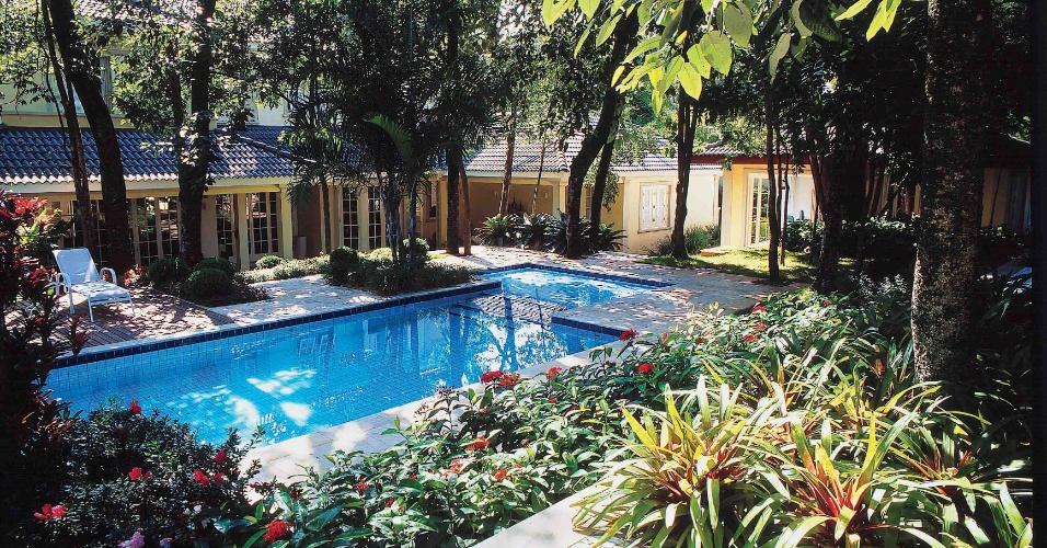 Em função das árvores existentes no jardim projetado pelo paisagista Marcelo Novaes, a piscina se localiza em um nível intermediário, entre a residência e o espaço gourmet. O ambiente serve para o relaxamento em um sombreado agradável cercado por maciços florais