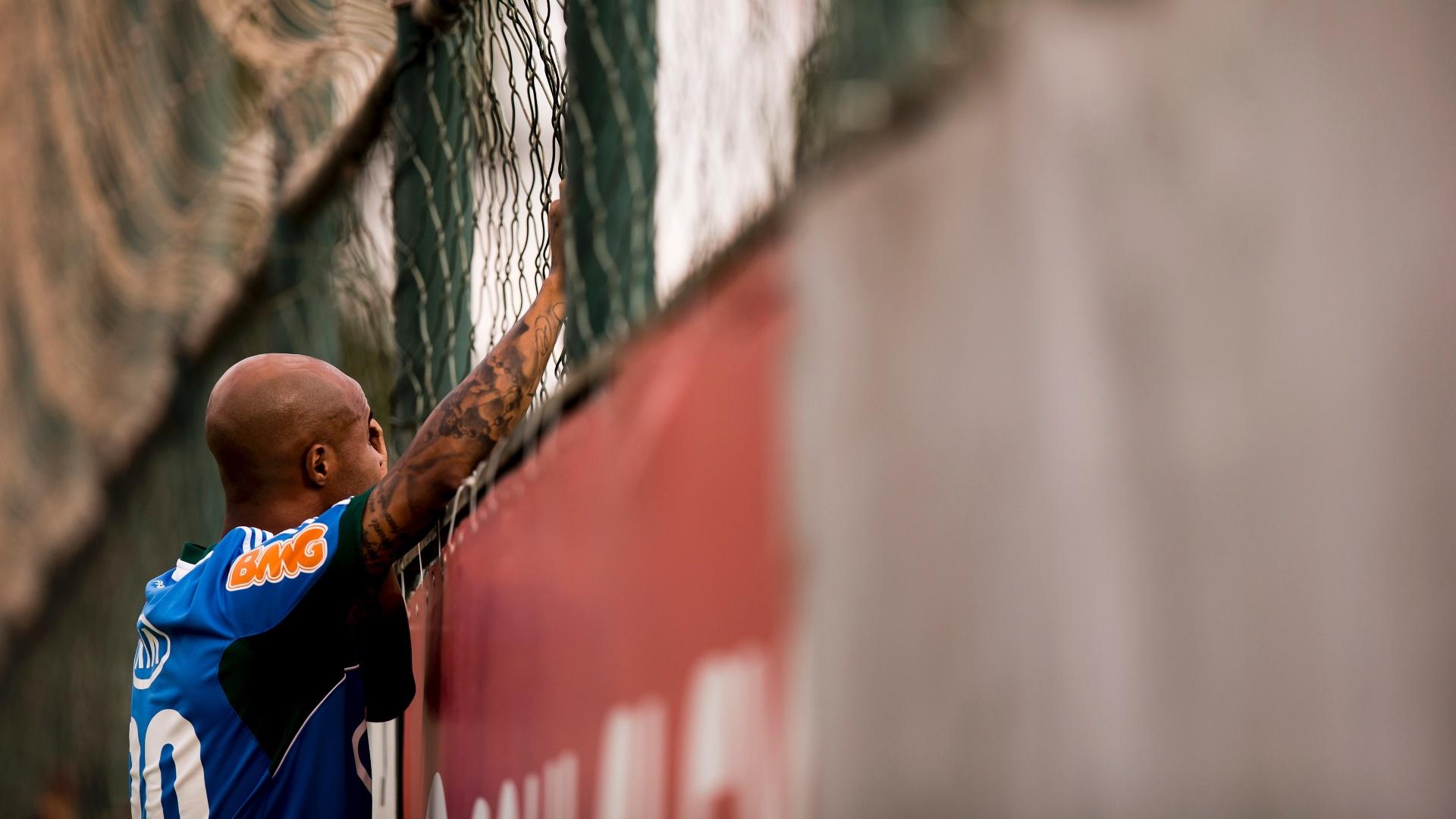 Marcos Assunção observa treino por cima da grade