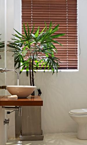 No lavabo do Apê Copacabana - datado dos anos 1950 e reformado pelo escritório de arquitetura House In Rio -, a bancada em peroba é combinada às louças brancas e ao piso de cimento queimado. Arremata o ambiente as persianas de madeira, que filtram a incidência solar