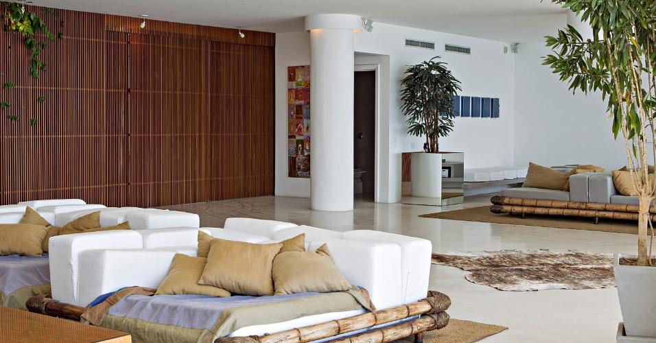 Numa visão geral do living do Apê Copacabana observa-se a amplitude do espaço, com 220 m², que ganhou piso de cimento queimado na cor areia e tem como destaque um painel de oito metros de comprimento, com portas de correr, feito em ripas de peroba mica que delimita os ambientes: cozinha, copa, lavabo e hall do elevador. Em primeiro plano, os enormes pufes desenhados pelos arquitetos do escritório House In Rio e executados em bambu e cordas de sisal