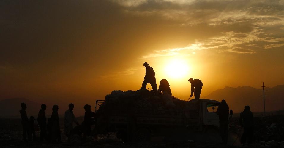 15.nov.2012 -  Catadores de lixo procuram objetos recicláveis com o pôr do sol ao fundo, em um subúrbio de Cabul, no Afeganistão