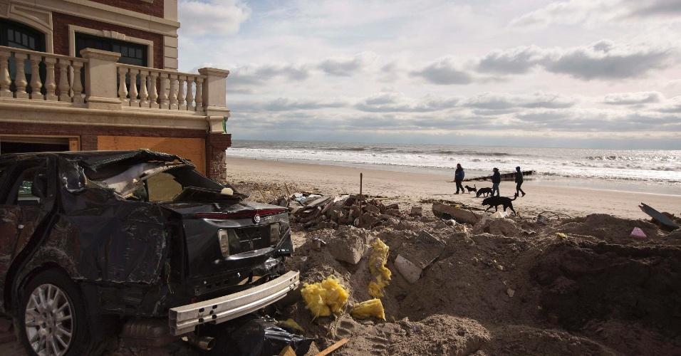 15.nov.2012 - Pessoas caminham na praia, ainda com estragos causados pelo furacão Sandy, de Belle Harbor, Nova York