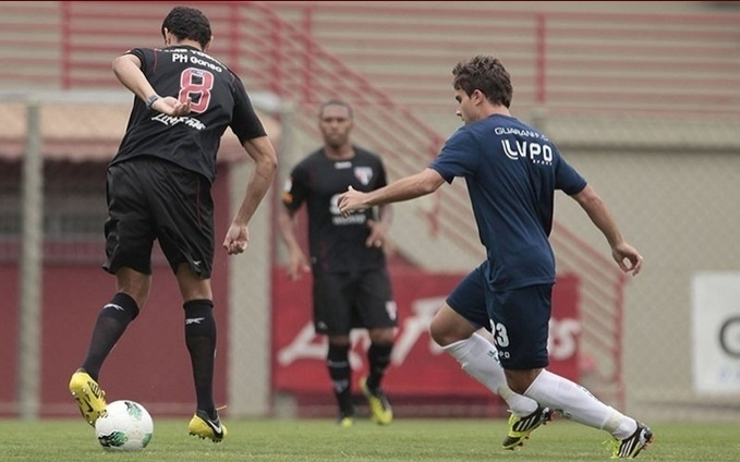 Ganso tenta o drible para cima de jogador do Guarani durante jogo-treino nesta quinta-feira