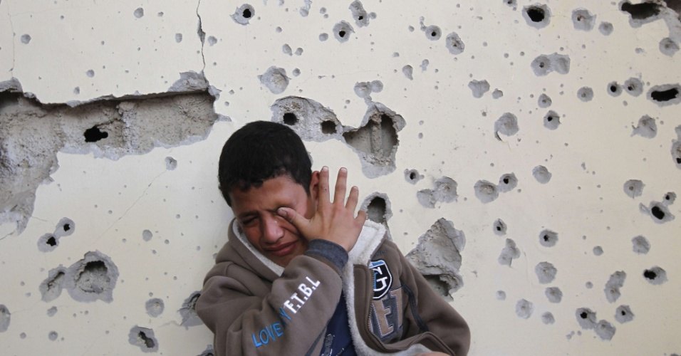 16.nov.2012 - Garoto palestino chora em frente a sua casa, que ficou parcialmente destruída após ataque aéreo israelense, em Beit Lahia, no norte da faixa de Gaza