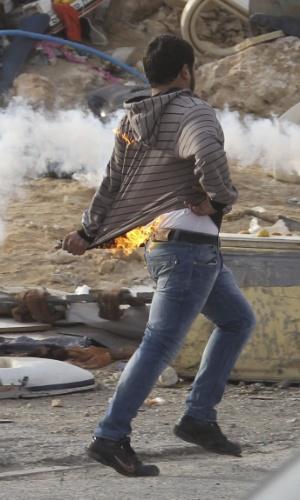 16.nov.2012 - Manifestante palestino tira a blusa em chamas depois que um coquetel Molotov explodiu em seu bolso durante protesto contra os ataques de Israel a Gaza, na Cisjordânia