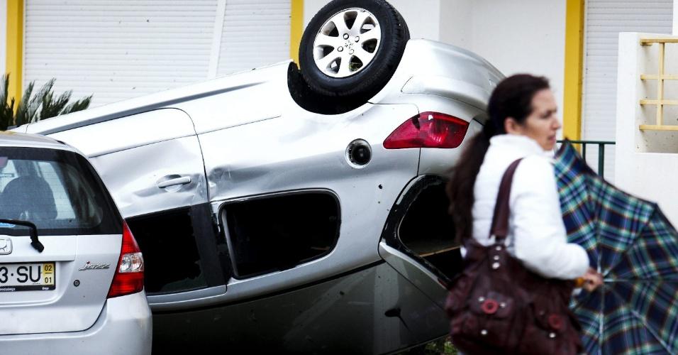 16.nov.2012 - Mulher passa ao lado de um carro que foi virado pelos fortes ventos em Silves, sul de Portugal. De acordo com as autoridades, oito pessoas ficaram feridas