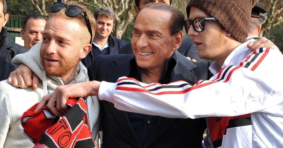 16.nov.2012 - O ex-primeiro ministro italiano Sivio Berlusconi é assediado por torcedore do Milan, time futebol italiano, durante visita à sede do clube, em Milanelli, perto de Milão