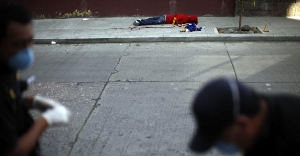 16.nov.2012 - Peritos analisam local onde homem foi assassinado na Cidade da Guatemala. Nos primeiros dez meses do ano, 4.936 pessoas foram mortas na Guatemala, de acordo com contagem de ONG do país