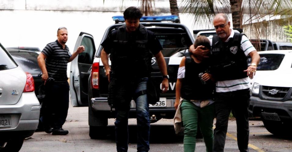 16.nov.2012 - Policial escolta Camila Camila Cukierman, 21, que foi sequestrada na madrugada desta sexta-feira (16), no bairro Peixoto, no Rio de Janeiro, ao chegar no prédio onde mora. A jovem foi resgatada e seguiu para a Delegacia Antissequestro (DAS). Ela usava um colete à prova de balas. Ainda não há informações sobre como ocorreu o resgate