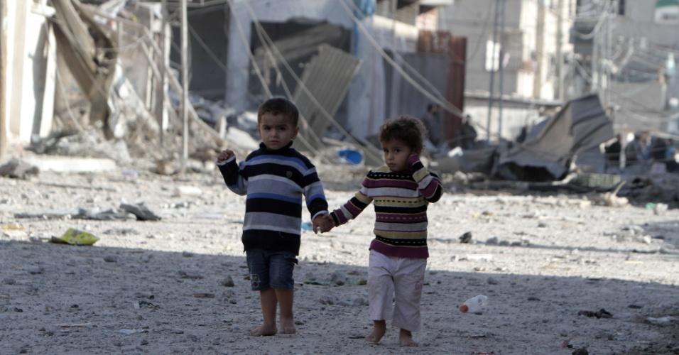 18.nov.2012 - Crianças palestinas andam entre edifícios destruídos após ataques aéreos israelenses na cidade de Rafah, no sul da Faixa de Gaza, neste domingo