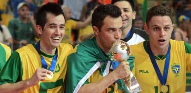 Ao lado dos companheiros, Falcão carrega e beija a taça da Copa do Mundo de futsal