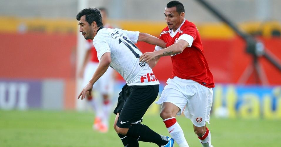 Douglas, do Corinthians, sofre com a marcação do argentino Guiñazu, do Internacional, durante partida pela 36ª rodada do Brasileirão