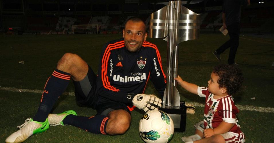 Goleiro Diego Cavalieri, do Fluminense, comemora a conquista do Brasileirão com a taça e o filho Enzo