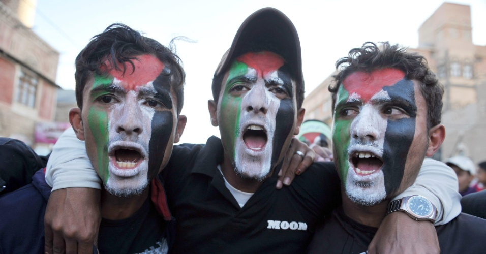 Manifestantes pintam seus rostos com as cores da bandeira da Palestina e gritam palavras de ordem em protesto que condena os ataques israelenses na Faixa de Gaza, em Sanaa, capital do Iêmen, neste domingo (18)