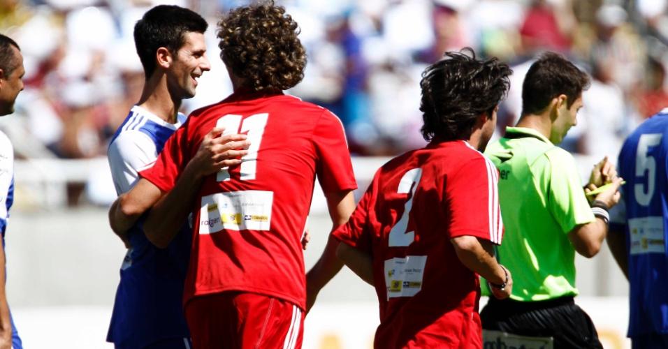 Novak Djokovic cumprimenta Gustavo Kuerten por gol marcado de pênalti em jogo festivo no Engenhão