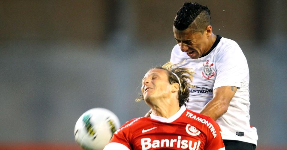 Ralf, do Corinthians, ganha jogada aérea contra o uruguaio Forlán, do Internacional
