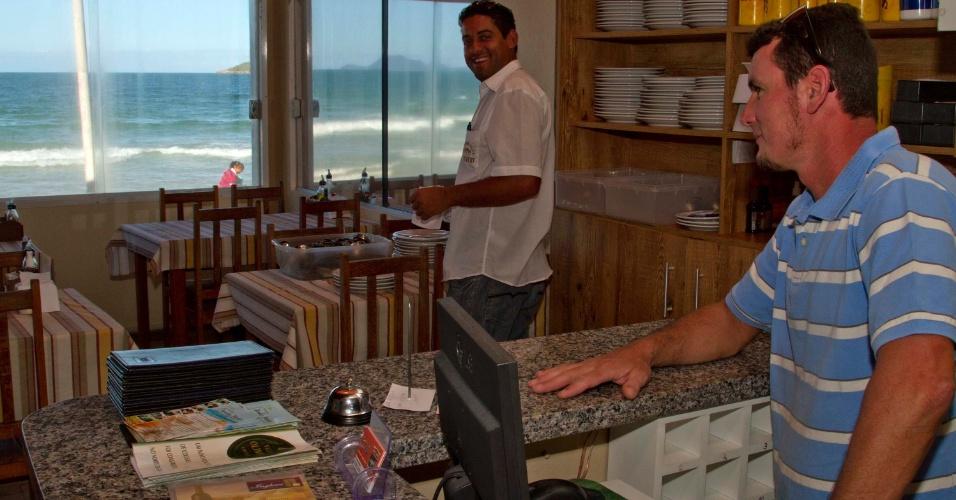 18.nov.2012 - O comerciante Rangel Fernando, 34 (de blusa azul), teve o restaurante assaltado três vezes em três meses, na praia dos Ingleses, região norte de Florianópolis, e reclama que a violência não se restringe à atual onda de ataques. Já o fluxo de turistas no feriadão não diminuiu na capital catarinense