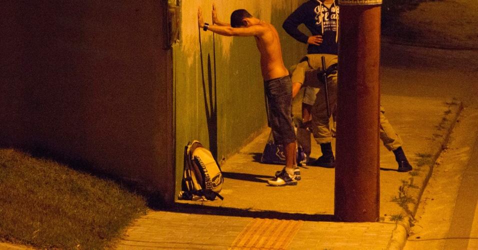 18.nov.2012 - Policiais revistam dois jovens que estavam em um ônibus que liga os bairros de Canasvieiras e Costão do Santinho na noite deste domingo.  A linha foi uma das que sofreram atentados nos últimos dias na capital catarinense
