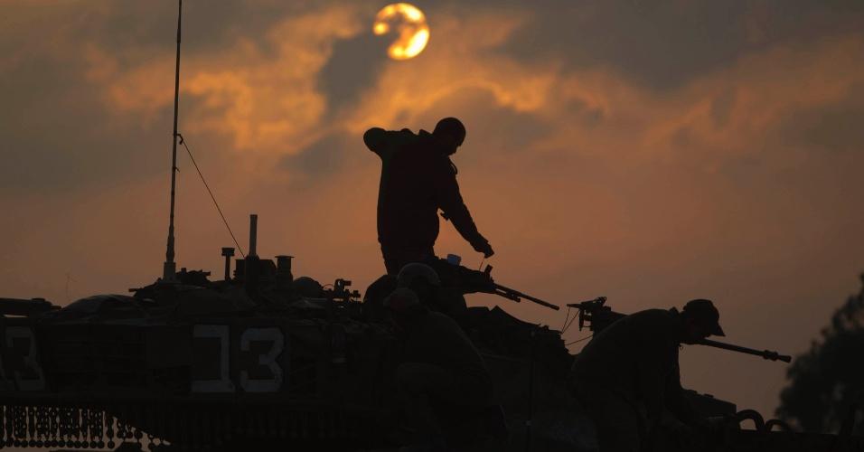 19.nov.2012 - Soldados israelenses em cima de um tanque, perto da fronteira de Israel com a Faixa de Gaza, na Cisjordânia
