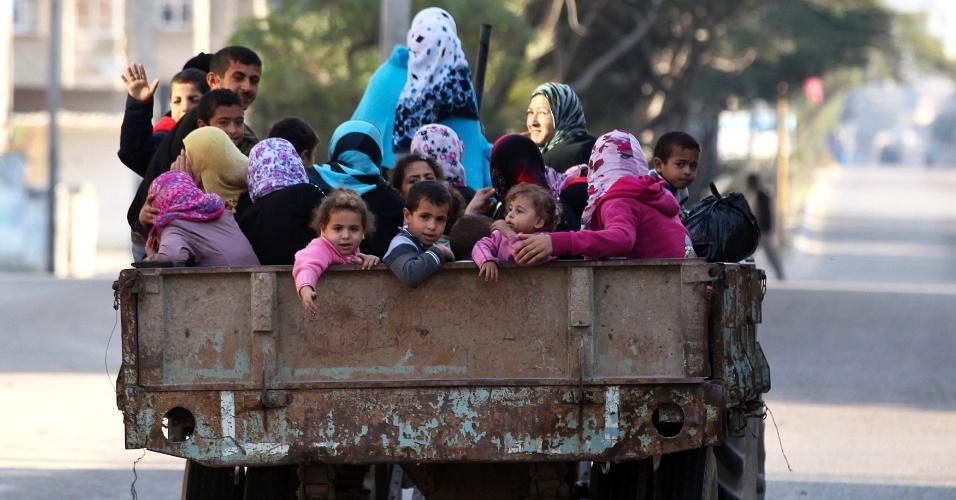 20.nov.2012 - Famílias palestinas pegam carona em um caminhão para uma escola das Nações Unidas na cidade de Gaza, na manhã desta terça-feira (20)