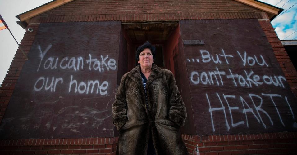 20.nov.2012 - Linda Restaino posa diante de sua casa em Staten Island, nos Estados Unidos. Ela morou no local por 35 anos e viu o local ser destruído pelo furacão Sandy. Na parede, uma mensagem escrita por seu filho, que diz