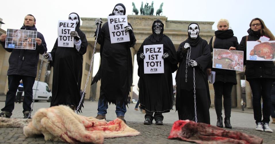 """21.nov.2012 - Membros do Peta, organização de ativistas dos direitos dos animais, protestam contra o uso de peles em frente ao Portão de Brademburgo, em Berlim, na Alemanha, nesta quarta-feira (21). Eles seguram cartazes com os dizeres """"Pelo é morte"""" e casacos de pele manchados com sangue artificial"""