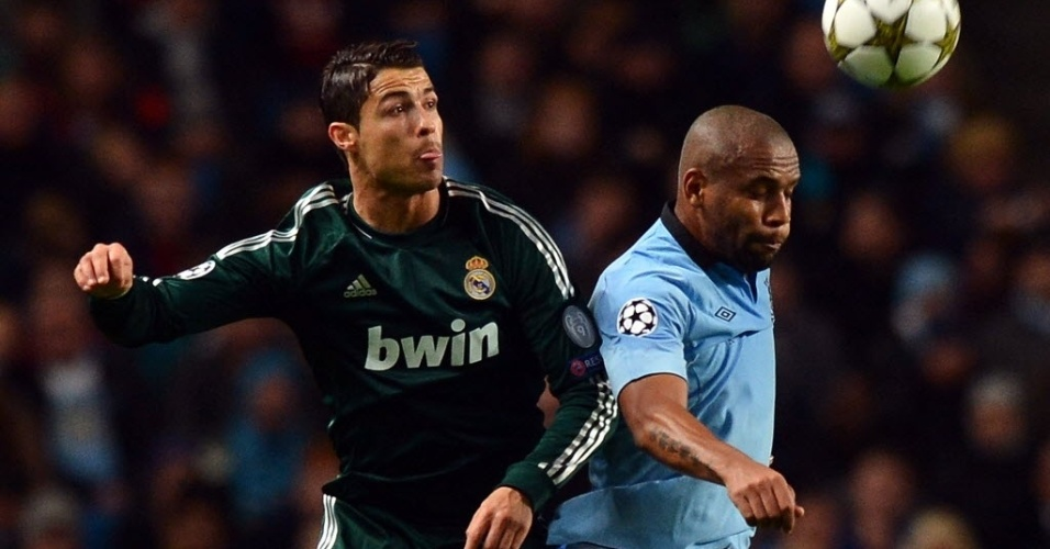 21.nov.2012 - Maicon (d), lateral brasileiro do Manchester City, disputa bola de cabeça com o português Cristiano Ronaldo, do Real Madrid, em partida da Liga dos Campeões