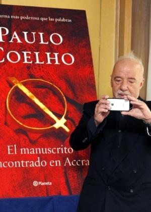 """O escritor Paulo Coelho fotografa jornalistas com seu iPhone durante lançamento de """"El Manuscrito Encontrado en Accra"""", na Espanha (21/11/12) - J.J. Guillén/EFE"""