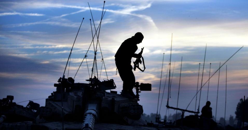 Silhueta de soldado israelense descendo de tanque, estacionado perto da faixa de Gaza