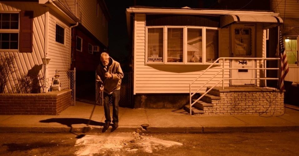 21.nov.2012 - Após quase um mês da passagem do furacão Sandy pelos Estados Unidos, moradores ainda limpam estragos da supertempestade. Em Broad Channel Queens, Nova Yorque, homem varre frente de sua casa