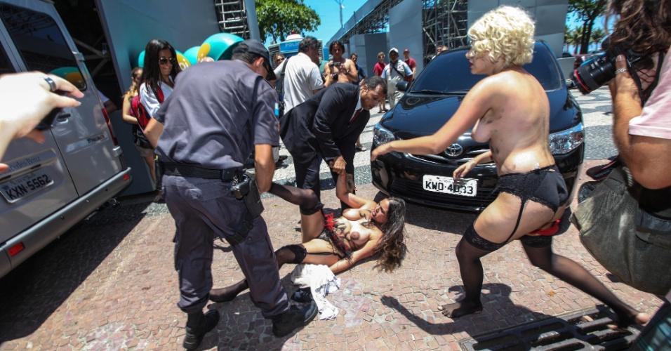 22.nov.2012 - As ativistas do grupo Femen Brazil Sara Winter (loira) e Anna (morena) protestam em frente ao hotel Copacabana Palace, na zona sul do Rio de Janeiro,contra o turismo sexual