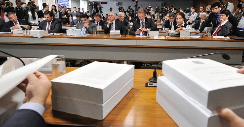 22.nov.2012 - Calhamaços de papel são colocados sobre a mesa da CPI do Cachoeira nesta quinta-feira. Os volumes são o relatório final de Odair Cunha (PT-MG)