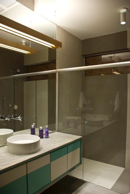 """Na residência reformada pelo escritório Arqdonini, o banheiro com 6,1 m² conta com bancada amplas e apenas com uma cuba. No ambiente, os """"retalhos"""" em revestimentos mais claros e o espelho generoso ampliam a área. Para compor com o décor, diante do espelho foi instalado um pendente feito em sarrafo de madeira - desenhado pelo escritório -, além do spot da Reka"""