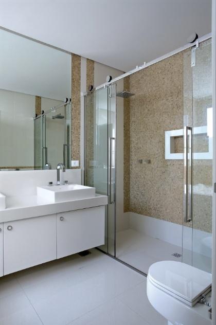 Com 6,5 m², o banheiro projetado pelo arquiteto Rogério Perez comporta área para dois chuveiros, bancada com duas cubas e gabinete e vaso. O espaço é claro e bem iluminado passando sensação de amplitude. Pastilhas mais escuras contrastam com o tom claro do ambiente, dando maior aconchego ao box autolimpante. Graças à automação é possível programar a temperatura da água previamente