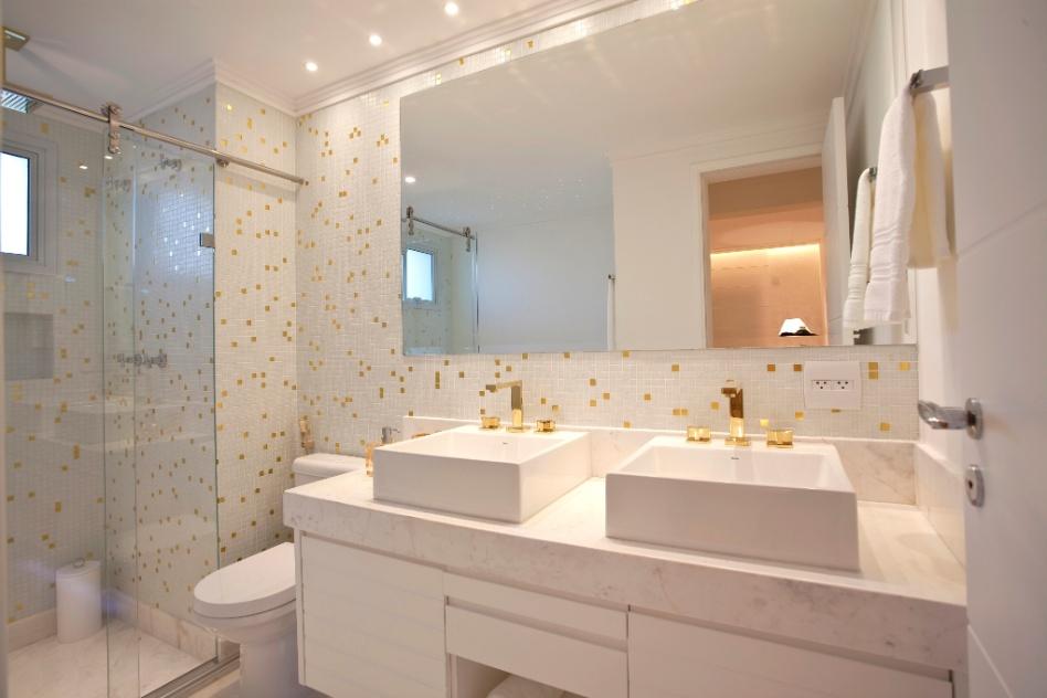 Pastilhas e metais dourados dão o leve toque clássico ao banheiro de 7,8 m², idealizado por Shenia Nogueira. A confortável bancada de mármore piguês apoia duas cubas da Deca e embute o gabinete, executado pela JSA Marcenaria. Bacia com caixa acoplada e ducha higiênica, em vez de bidê, racionalizam o espaço. No boxe, o nicho para xampus otimiza a área útil do banho