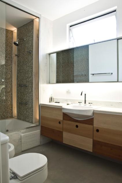 O aproveitamento do espaço é o ponto alto da proposta do escritório Arqdonini. Nela, a instalação do espelho e da bancada com cuba de embutir sob a janela tirou partido da luz natural, racionalizando os 6,34 m² do banheiro. Sob o tampo, o amplo gabinete compõe com piso em porcelanato. Dispostos em frente ao lavatório, o bidê e a bacia com caixa acomplada - da Deca - ficam ao lado da área do box, revestida com porcelanato estampado Navarti e iluminada indiretamente pelas luzes instaladas em dois nichos