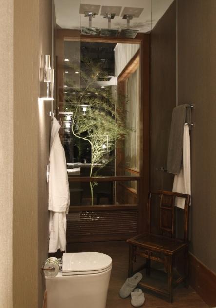 Por se tratar de um banheiro (5,4 m²), situado em um pequeno loft, a arquiteta Ana Rita Sousa e Silva dividiu-o em duas áreas, cortadas pela circulação entre o quarto e a sala. Deste ângulo, o vaso sanitário e a ducha - que detém uma porta -, são lateralmente integrados ao jardim por uma esquadria de vidro. Nos revestimentos, o porcelanato amadeirado do piso recobre também as paredes da área molhada...