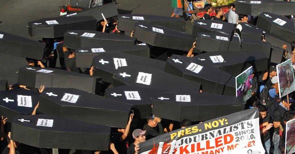 23.nov.2012 - Jornalistas filipinos carregam caixões falsos simbolizando as vítimas de um massacre ocorrido em 2009, nesta sexta-feira (23) em Manila. No episódio, 57 pessoas foram mortas do lado de fora do palacio presidencial em Manguindanao. O ex-prefeito Andal Ampatuan Jr. é suspeito de ser o mandante do crime, e aguarda julgamento