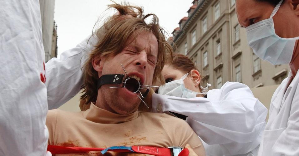 23.nov.2012 - Membro do grupo Verein gegen Tierfabriken (Associação Contra Fábricas de Animais) simula testes médicos realizados com animais durante protesto em Viena (Áustria), nesta sexta-feira (23)