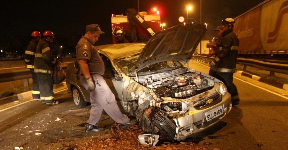 23.nov.2012- Policiais inspecionam veículo que capotou após bater em placa de sinalização na marginal Tietê, em São Paulo (SP)