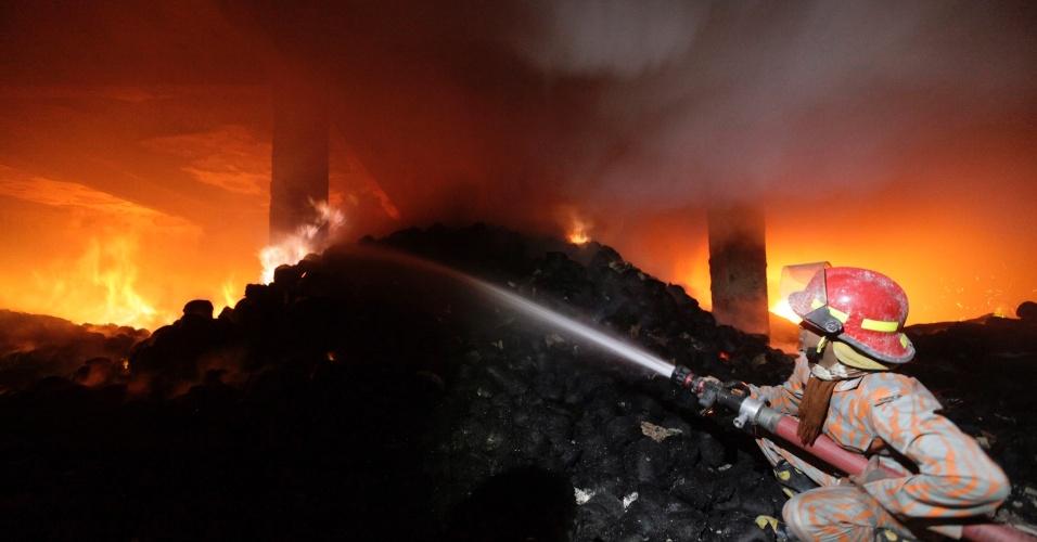24.nov.2012 - Bombeiro tenta controlar as chamas do incêndio que consumiu uma manufatura, nesta sábado (24) nos arredores de Dacca (Bangladesh). Pelo menos sete pessoas morreram e cem ficaram feridas
