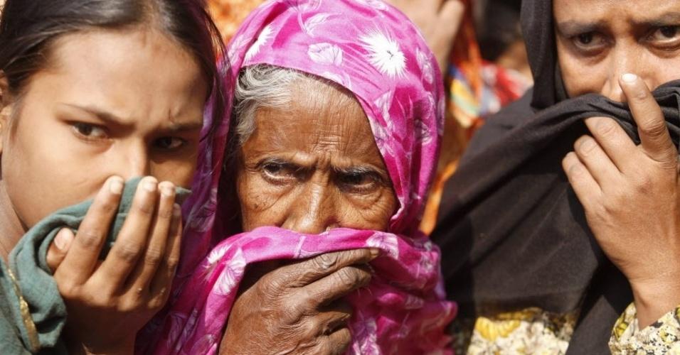 25.nov.2012 - Aldeãs cobrem os narizes para evitar o mau cheiro de corpos carbonizados após incêndio em fábrica no subúrbio de Dacca, capital de Bangladesh