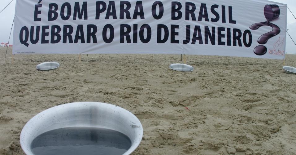 25.nov.2012 - Manifestantes da ONG Rio de Paz fazem manifestação na praia de Copacabana neste domingo (25), no Rio de Janeiro, contra a nova lei de distribuição dos royalties do petróleo