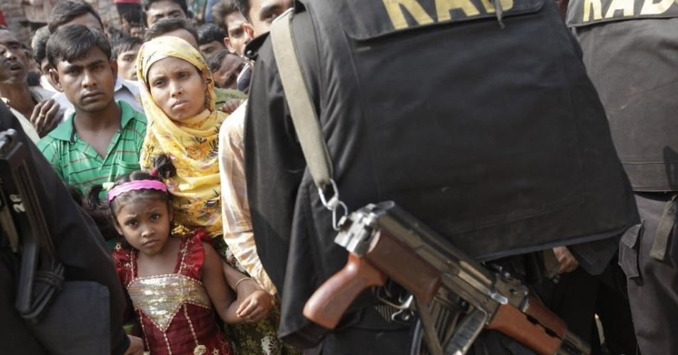25.nov.2012 - Policiais guardam entrada de fábrica incendiada e impedem acesso do público ao local, na periferia de Dacca, capital de Bangladesh. O fogo começou na noite de sábado (24), supostamente por um curto-circuito, e matou pelo menos 121 pessoas