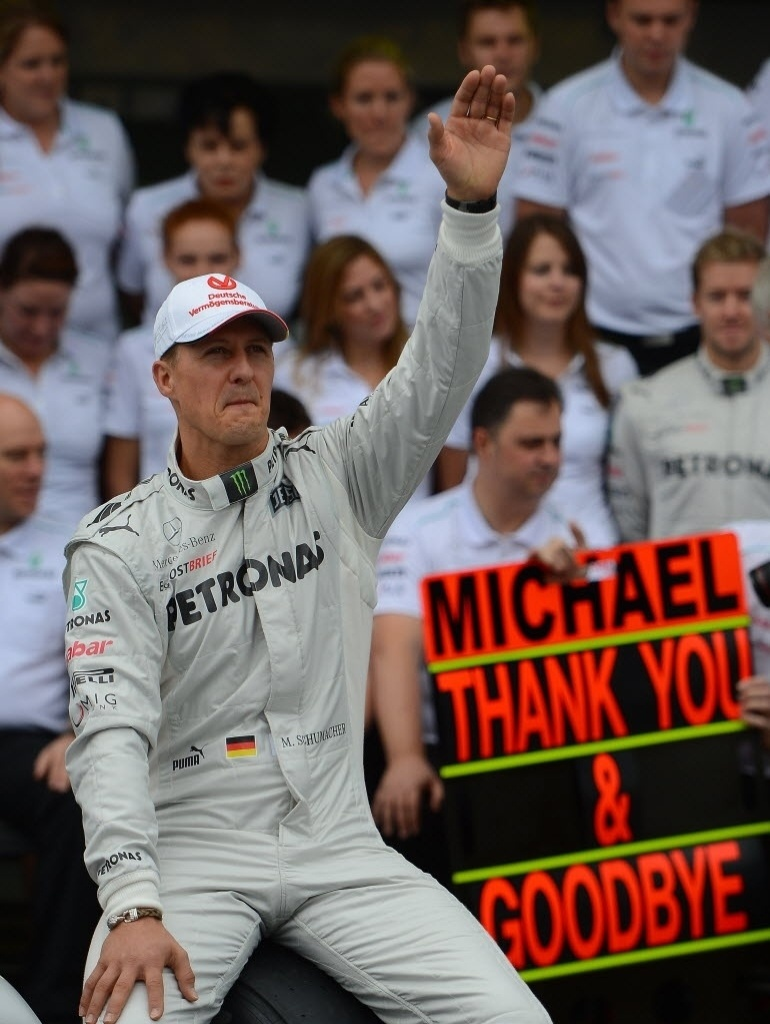 Schumacher acena para o público enquanto recebe homenagem no dia de seu último GP de Fórmula 1