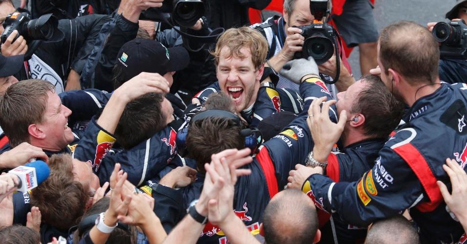 Sebastian Vettel é abraçado pelos seus companheiros de Red Bull após confirmar a conquista do seu terceiro título da Fórmula 1