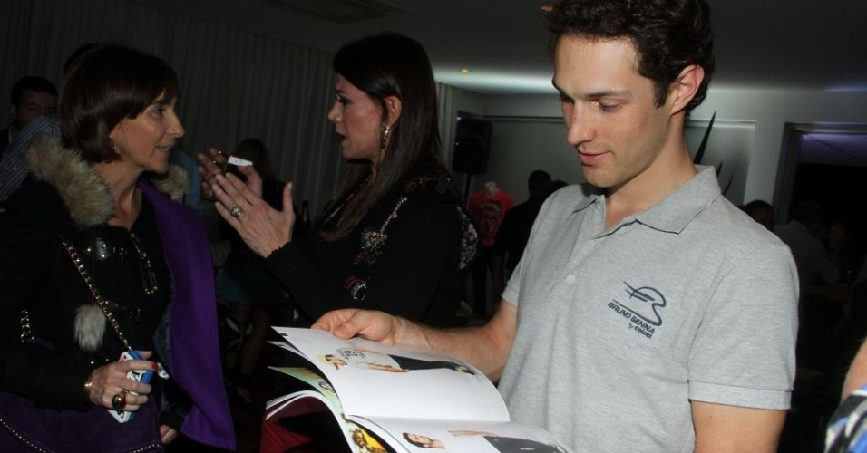25.nov.2012 - Bruno Senna analisa catálogo da Colcci no lançamento de sua coleção para a grife