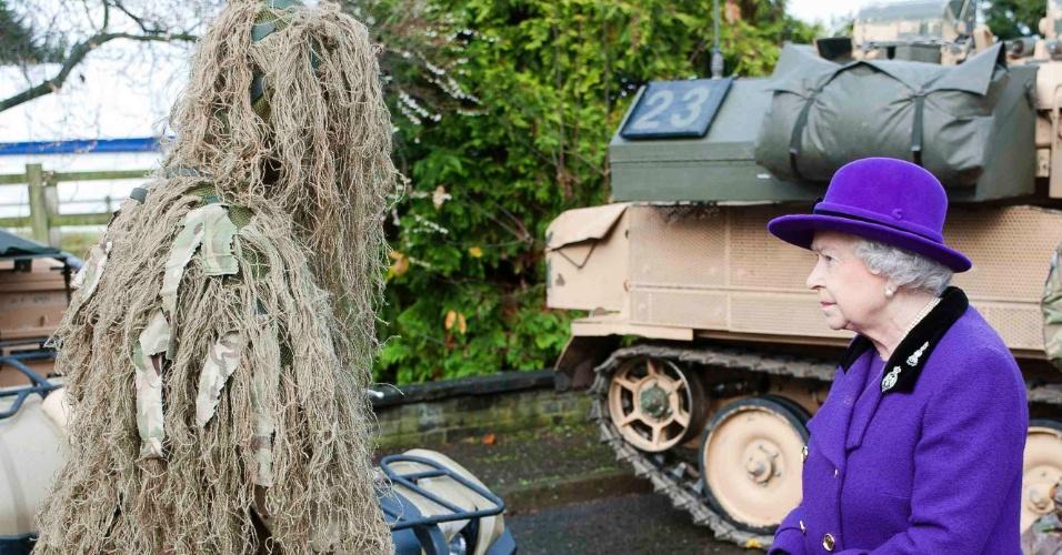 26.nov.2012 - A rainha Elizabeth 2ª conhece um franco-atirador do Exército com camuflagem usada nos campos de batalha, durante visita ao quartel de Combermere, em Windsor, na Inglaterra