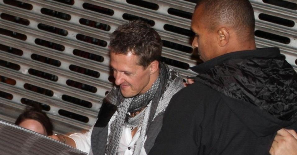 26.nov.2012 - Cercado por seguranças, Michael Schumacher deixa balada de encerramento da Fórmula 1 em São Paulo