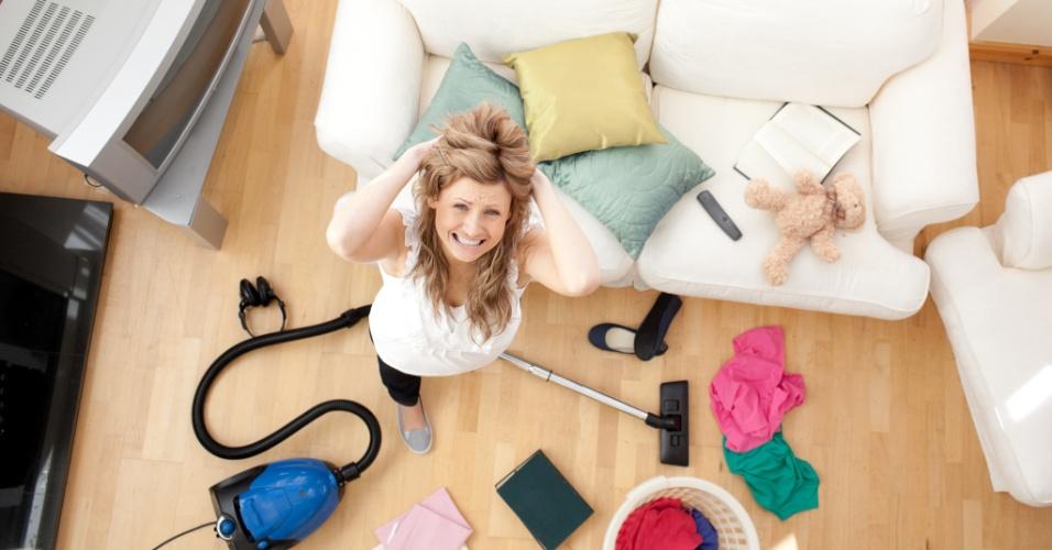 mulher arruma a bagunça da sala, mulher arruma brinquedos e roupas no chão, sofá, aspirador, mulher estressada arrumando a casa